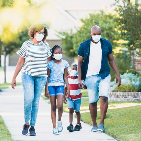 A family wearing masks walks together outdoors